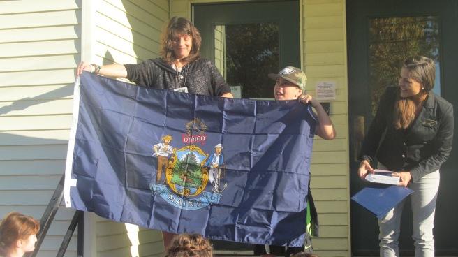 Sen Keim and student, Gabriel Damon, opening the flag